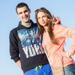 A young Russian man wearing a Big Apple sweater as he walks with his girlfriend at the Alfa Future People festival.