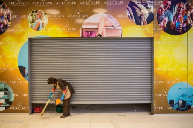 A woman cleaning in front of a store that is still a few days or weeks away from opening.