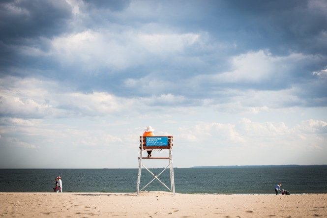 A Belarusian woman studying English in a lifeguard chair at Coney Island.
