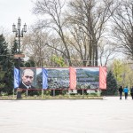 A photo of Vladimir Putin on the main square near the regional government buildings.