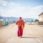 A Buddhist student walking to his village home located next to the Datsan.