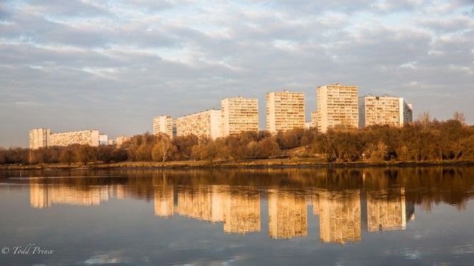 Soviet-era panel housing at the city edge cast a reflection in the Moscow River at sunset.