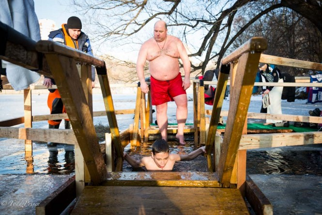 A Russian father watching his son dip into the cold Moscow River during Epiphany celebration.