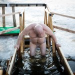 A Russian man slowly enters the water as a cross dangles from his neck.