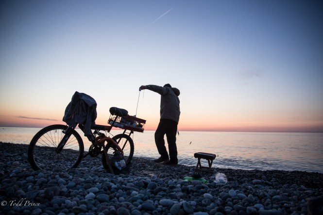 Fisherman in Batumi with his bike at sunset.