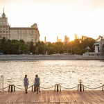 Two girls tap dancing as the sun sets over the Moscow River.
