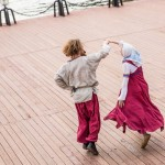 A couple teaching Russian folk dancing.