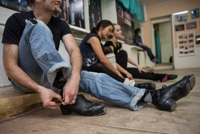 Irish dance students in Kazan lacing up their shoes.