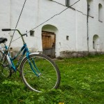 A bicycle chained to the electricity wires running to a church.