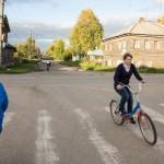 A young girl biking around Kargopol town after school.