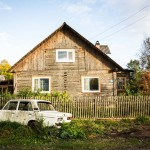 A Lada car with no back window sits in front of a wooden home in Kargopol.