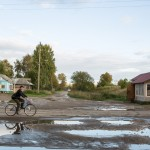 A man biking by a muddy road.