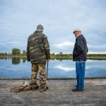 A fisherman talking to his friend at a pier in Kargopol.