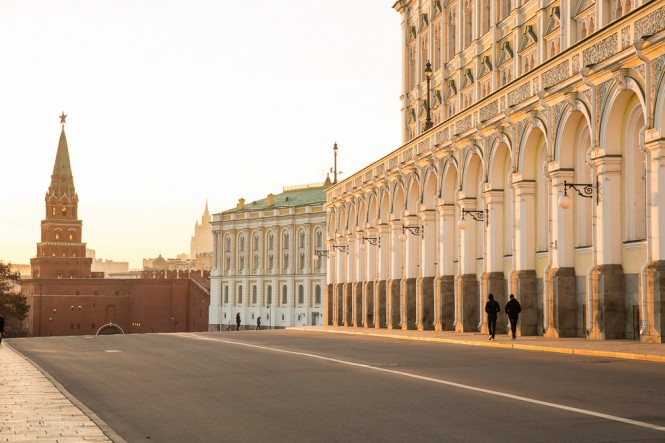 Two visitors passing the Grand Kremlin Palace at sunset time on their way to the exit at Borovitskaya Tower in the distance.