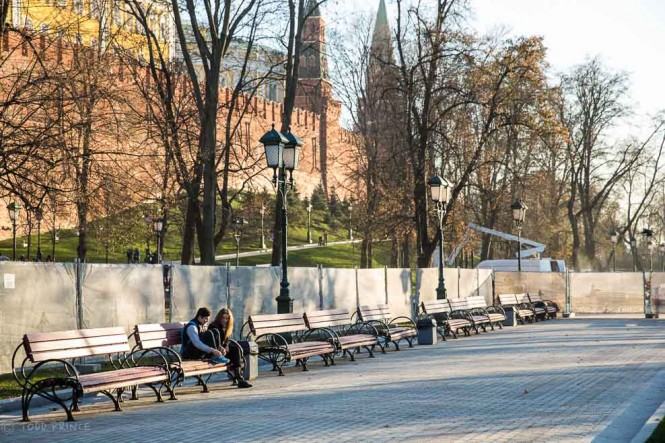 A couple sits alone in the garden outside the Kremlin Walls shortly before sunset.