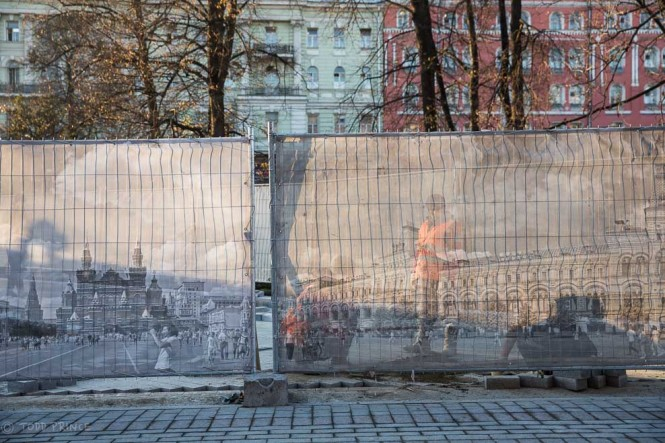 City workers repair the pedestrian paths cutting through the gardens in front of the Kremlin Walls. A fence covered with photos of Red Square partially hides the workers.