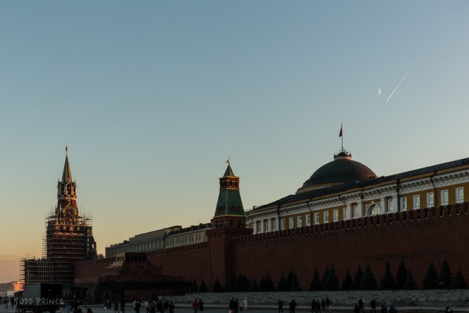 A plane flying over the Kremlin and under the moon at sunset time in Moscow.