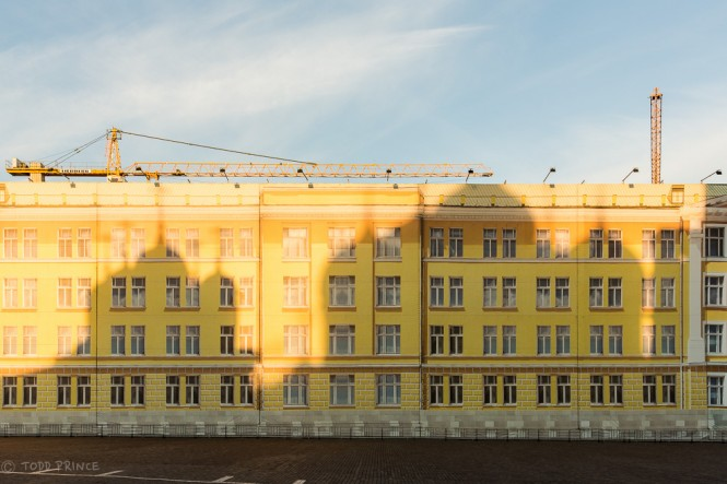 The Cupolas from the Twelve Apostles' Church and Assumption Cathedral cast shadows on a Kremlin building under maintenance.
