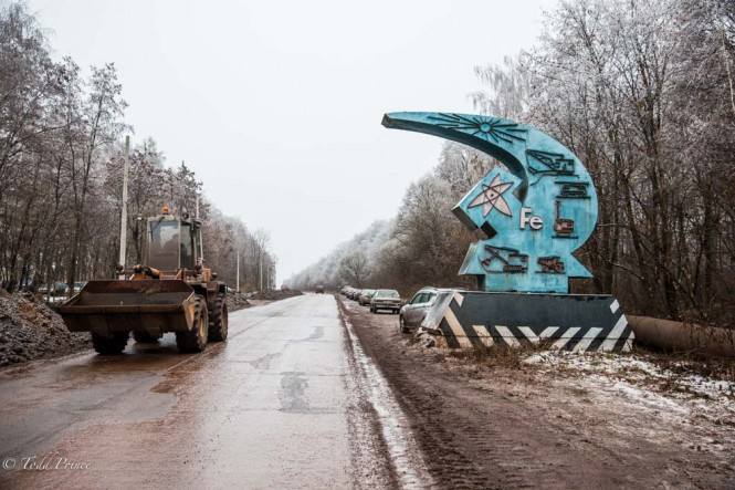 Heavy machinery passes a Soviet emblem welcoming people to one of Russia's largest iron ore mines.