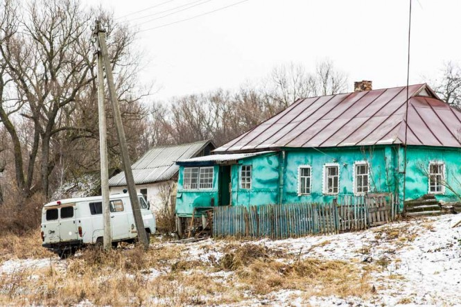 An old Russian ambulance in front of a Kursk village home.