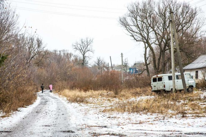 Two villages pass by an ambulance as they walk along the icy road.