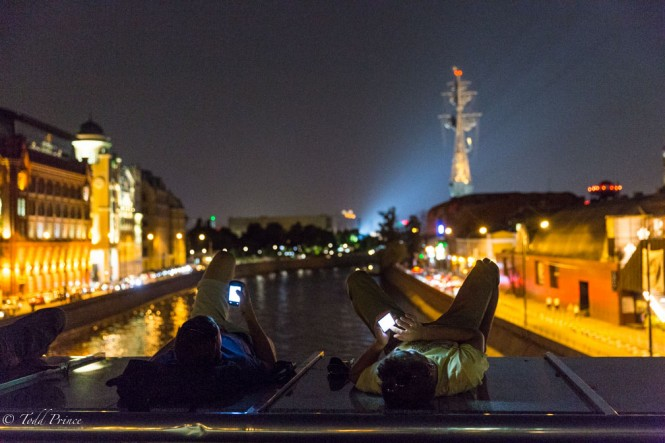 Two Russian youth checking mobile phones as they relax on a foot bridge above the Moscow River.