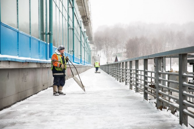 A city worker clearing snow on a pedestrian bridge.