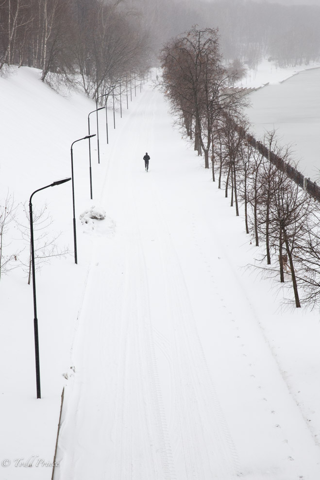 A man jogging along the Moscow River during the snow storm.