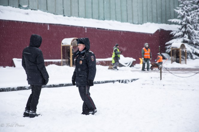 Cops chatting as worker clear the snow for the Honor Guard in front of the Kremlin Wall.