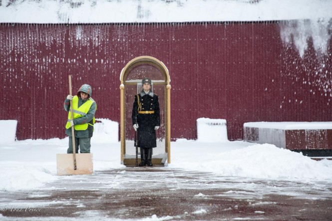 A city worker shoveling snow in front of the honor guard.