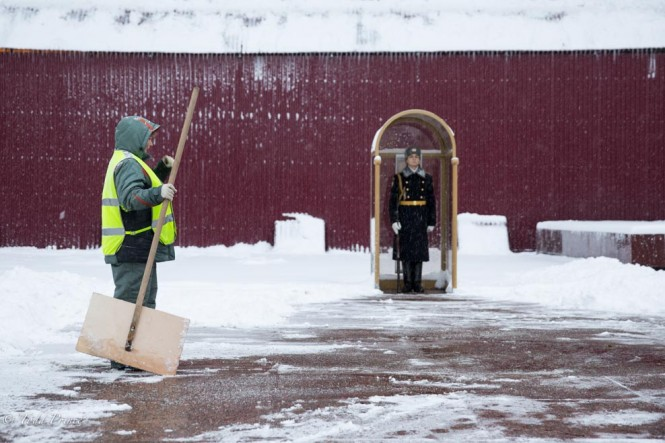 A city worker takes a pause from shoveling snow in front of the honor guard.