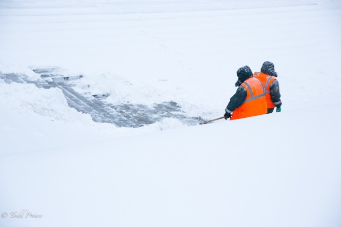 Two middle-aged women clearing snow near the Kremlin.