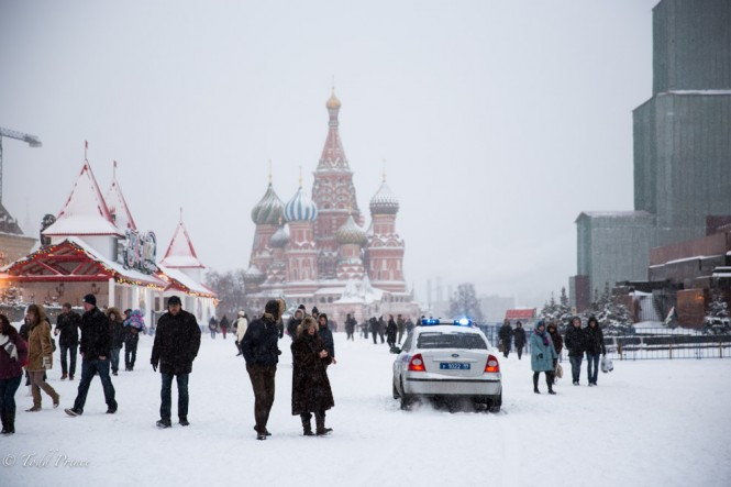 A police car rides through the snow on Red Square.