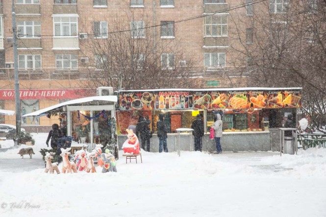 Christmas decorations for sale sit in the snow as workers in the background make falafels.