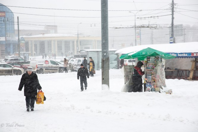 A newspaper seller stands amid piles of snow near a Moscow metro station.