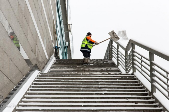 A city worker tossing snow off the pedestrian bridge.