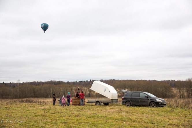 A family preparing to take off in a hot air balloon as another one flies into the distance.