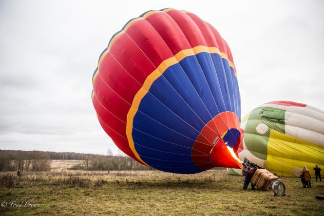 Workers about to finish filling up a hot air balloon.