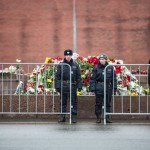 Cops stand in front of a pile of flowers near the spot where Nemtsov was killed.