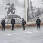 Police standing near the bridge against a facade of Moscow photos.