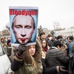 A Russian woman holding a photo critical of Putin.