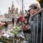 A man gazing at flowers left for Nemtsov during rally.
