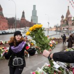 A rally participant handing flowers to woman to leave near sight of Nemtsov's murder.