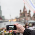 A man photographing the flowers left for Nemtsov near St. Basil's.