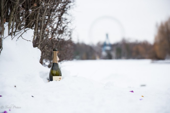 A bottle of champagne sticks out of the snow on New Year's day. Confetti is sprinkled around the bottle atop the snow.