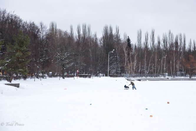 A Russian man pushing a baby carriage through the snow at Izmailovsky Park on New Year's Day as evidence of fireworks lie on top of the snow.