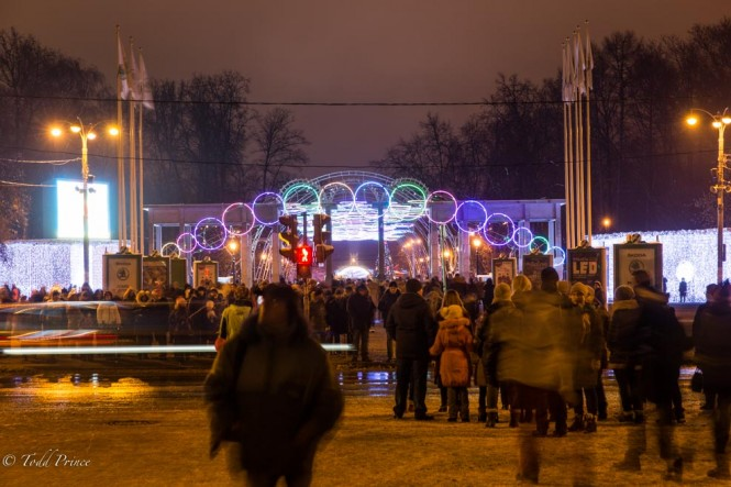 Russians heading toward the entrance to Sokolniki Park, which is decorated in various lights.