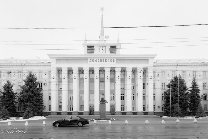 A black mercedes sits in front of the House of the Soviets in Tiraspol as a bust of Lenin looks on.