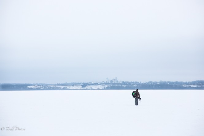 Dima walking out onto Lake Pleshcheyevo, a monastery visible on the shore in the background.