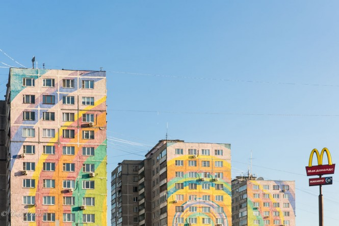 Late Soviet-era housing covered in a rainbow painting to hide the original gray facade.